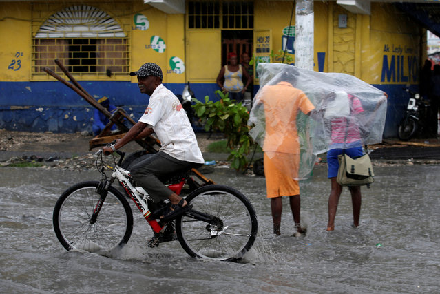 A man rides a bicycle as two women protect themselves from rain after Hurricane Matthew in Les Cayes, Haiti, October 17, 2016. (Photo by Andres Martinez Casares/Reuters)
