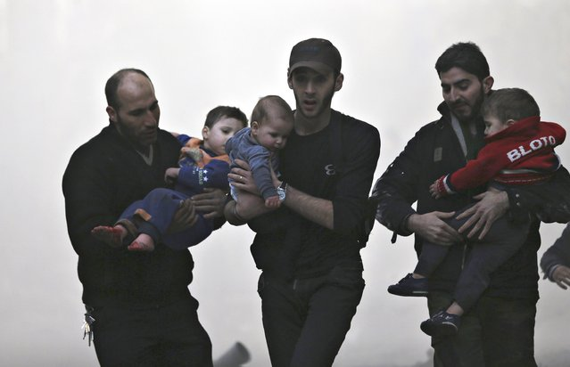 Men rescue children at a site hit by what activists said was an air strike by forces of Syria's President Bashar al-Assad  in the Duma neighbourhood of Damascus December 27, 2014. (Photo by Bassam Khabieh/Reuters)