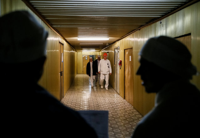 Employees walk through the corridor of the stopped third reactor at the Chernobyl nuclear power plant in Chernobyl, Ukraine April 20, 2018. (Photo by Gleb Garanich/Reuters)