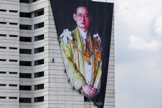 Workers install a portrait of Thailand's late King Bhumibol Adulyadej at a building in Bangkok, Thailand, October 21, 2016. (Photo by Athit Perawongmetha/Reuters)