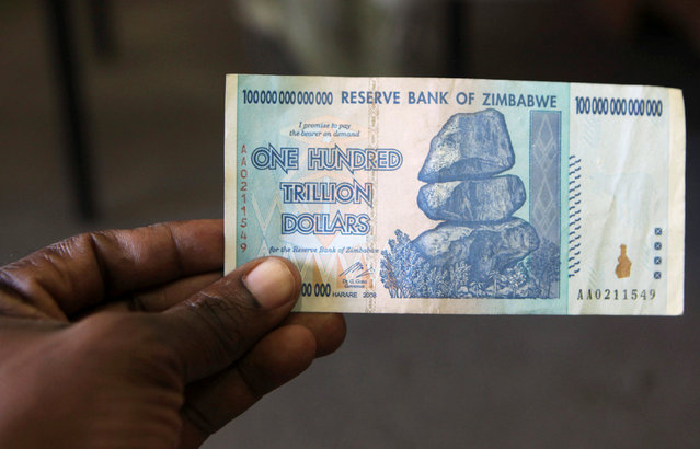 A man holds up for a picture a one hundred trillion Zimbabwean dollars note inside a shop in Harare, Zimbawe, June 12, 2015. (Photo by Philimon Bulawayo/Reuters)