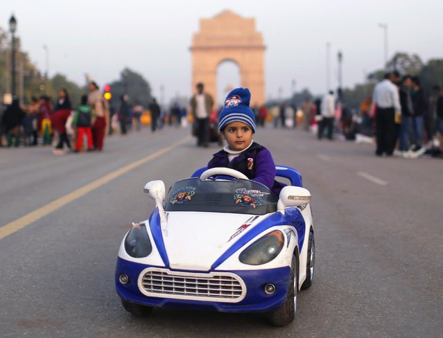 A child rides in a remote-operated toy car at the India Gate in New Delhi January 5, 2015. (Photo by Anindito Mukherjee/Reuters)