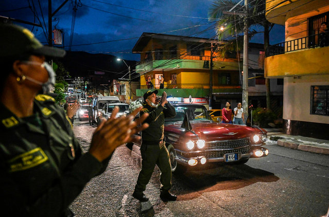 A police officer sings as a hearse drives along a street as part of a campaign sponsored by the Colombian police and a funerary home to raise awareness during the new coronavirus pandemic in Envigado, Antioquia, Colombia, on April 1, 2020. More than 20,000 cases of COVID-19 were registered in Latin America and the Caribbean by Wednesday, according to an AFP tally using information provided by national health authorities and the World Health Organization. (Photo by Joaquin Sarmiento/AFP Photo)