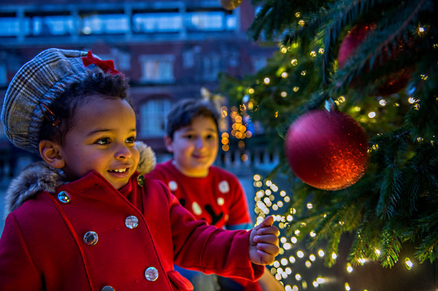 Children explore a Christmas tree outside the Royal Albert Hall in London, United Kingdom on December 9, 2020, as the building opened its doors for the first time in nearly nine months. (Photo by Annabel Moeller/The Guardian)