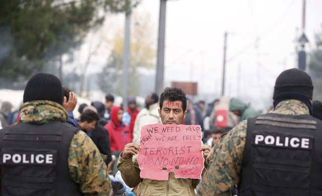 A migrant protests in front of police at the border with Greece, near Gevgelija, Macedonia November 25, 2015. Countries along the Balkan route taken by hundreds of thousands of migrants seeking refuge in western Europe last week began filtering the flow, granting passage only to those fleeing conflict in Syria, Iraq and Afghanistan. (Photo by Stoyan Nenov/Reuters)