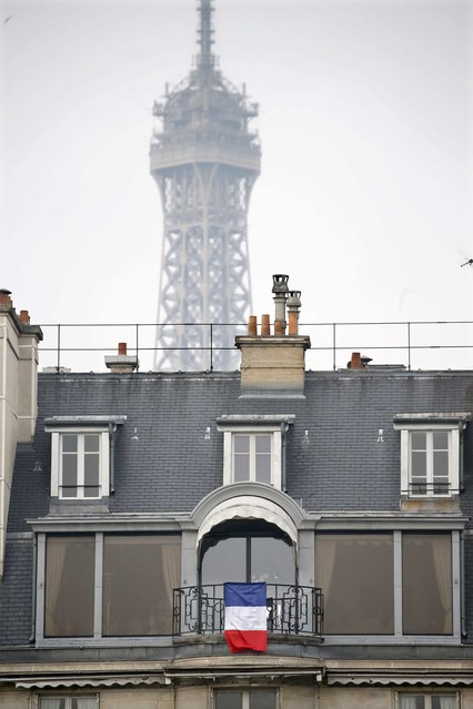 A French flags is seen on a balcony in Paris in front of the Eiffel tower, France, November 27, 2015 as the French President called on all French citizens to hang the tricolour national flag from their windows on Friday to pay tribute to the victims of the Paris attacks during a national day of homage. (Photo by Charles Platiau/Reuters)