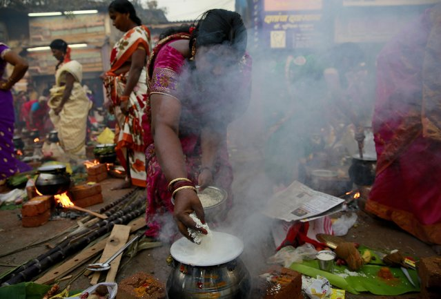 A Tamil Hindu woman cooks special food to celebrate the harvest festival of Pongal at Dharavi, one of the world's largest slums, in Mumbai, India, Thursday, January 15, 2015. (Photo by Rafiq Maqbool/AP Photo)