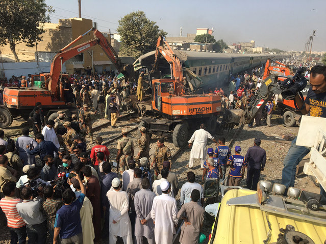 Rescuers workers use heavy machinery on the car of a train which crashed outside Karachi, Pakistan November 3, 2016. (Photo by Akhtar Soomro/Reuters)