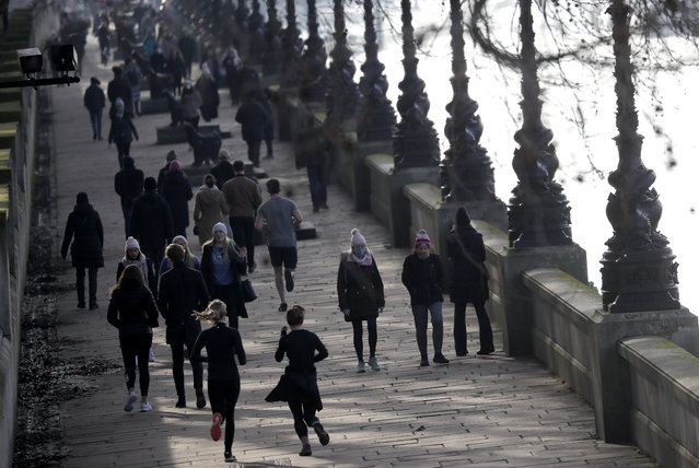 People exercise along the bank of the River Thames in London, Saturday, January 23, 2021 during England's third national lockdown since the coronavirus outbreak began. The U.K. is under an indefinite national lockdown to curb the spread of the new variant, with nonessential shops, gyms and hairdressers closed, and people being told to stay at home. (Photo by Kirsty Wigglesworth/AP Photo)