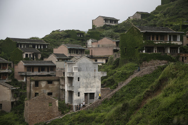 In this May 19, 2018, photo, tourists walk up narrow stairs winding through the abandoned fishing village of Houtouwan on the remote island of Shengshan, 90 kilometers off the coast of Shanghai. (Photo by Sam McNeil/AP Photo)