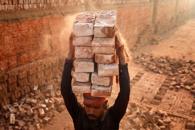 A man stacks more bricks on his head while working at in brickfields Narayanganj near Dhaka Bangladesh on January 02, 2021. (Photo by Kazi Salahuddin Razu/NurPhoto via Getty Images)