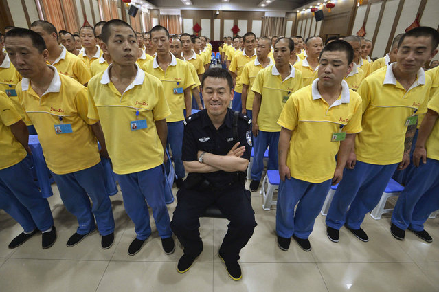 Drug addicts stand waiting for officials to enter as a policeman sits in the middle before a performance, ahead of International Day Against Drug Abuse and Illicit Trafficking, at a drug addiction rehabilitation centre in Taiyuan, Shanxi province, June 25, 2013. (Photo by Jon Woo/Reuters)