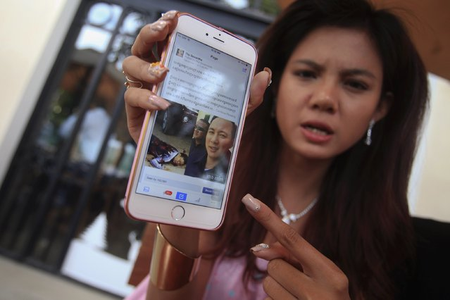 Online activist Thy Sovantha, 19, shows a Facebook page with images of dead businessman Ung Meng Cheu (L) and Thorng Sarat, a tycoon police suspect of masterminding the shooting in Phnom Penh December 11, 2014. Security camera footage of the shooting went viral in Cambodia, illustrating the burgeoning power of social media in a youthful country where internet usage has soared in recent years. (Photo by Samrang Pring/Reuters)