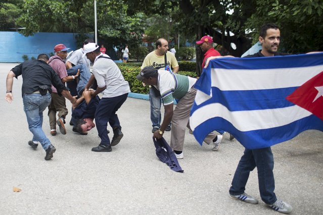 Cuban security personnel detain a supporter of the Ladies in White dissident group (L), during a protest on International Human Rights Day, Havana, December 10, 2015. (Photo by Alexandre Meneghini/Reuters)