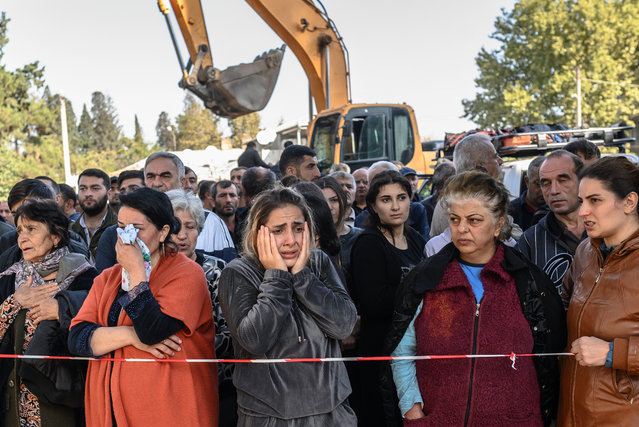 People stand behind caution tape as rescuers search for victims or survivors at the blast site hit by a rocket during the fighting between Armenia and Azerbaijan over the breakaway region of Nagorno-Karabakh, in the city of Ganja, Azerbaijan, on October 11, 2020. (Photo by Bulent Kilic/AFP Photo)