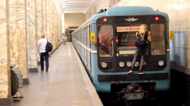 Rush-hour in Russia means one thing for this daredevil: train surfing! The 19-year-old daredevil who goes by the name Kobzarro started train surfing aged 15 as a way of escaping an oppressive family life. Here Kobzarro can be seen hanging precariously from the back of the Moscow Metro. (Photo by Caters News Agency)