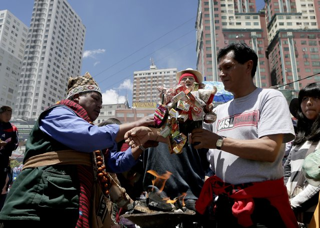 "A witch doctor blesses an ""Ekeko"", the god of fortune, during the ""Alasitas"" fair in La Paz January 24, 2015. (Photo by David Mercado/Reuters)"