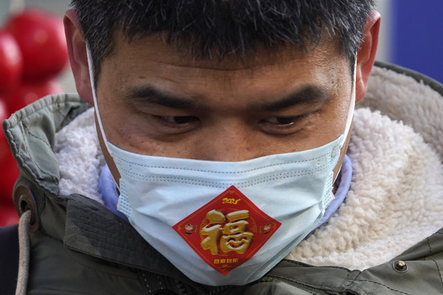 "A street vendor wears a mask with a sticker which reads ""Fortune"" at a street stall near Wangfujing on the fourth day of the Lunar Chinese New Year in Beijing on Monday, February 15, 2021. (Photo by Ng Han Guan/AP Photo)"