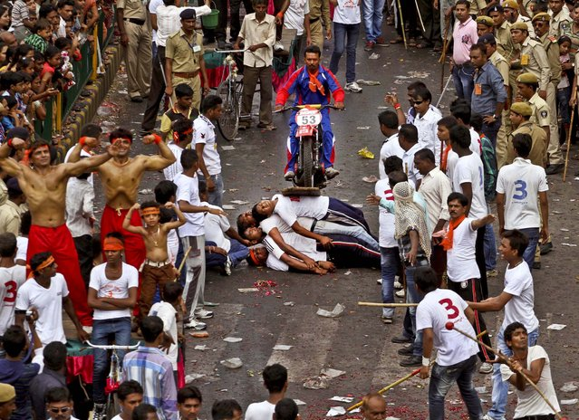 Men perform a stunt as they participate in the annual chariot procession of Hindu god Lord Jagannath in Ahmadabad, India, on July 10, 2013. (Photo by Ajit Solanki/Associated Press)