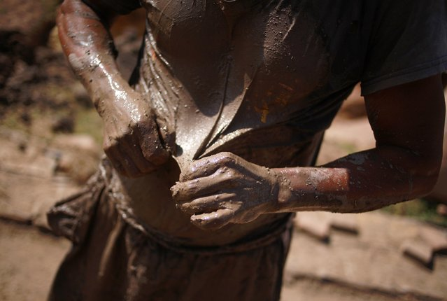 A worker holds his shirt which is covered in mud while working at a brick factory in Tixtla, on the outskirts of Chilpancingo, in the Guerrero state, January 26, 2015. (Photo by Jorge Dan Lopez/Reuters)