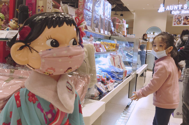 A girl wears a face mask to help curb the spread of the coronavirus and looks at a doll wearing the same at a department store in Taipei, Taiwan, Saturday, February 27, 2021. (Photo by Chiang Ying-ying/AP Photo)