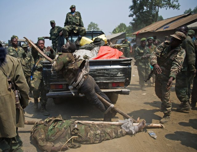 The bodies of two alleged rebel fighters are dumped out of the back of a pickup truck by soldiers in the Democratic Republic of the Congo on July 16, 2013. According to the army, one of the men was Ugandan and the other Rwandan, but they could not produce the identity cards that they claimed to have seen proving this. (Photo by Phil Moore/AFP Photo)