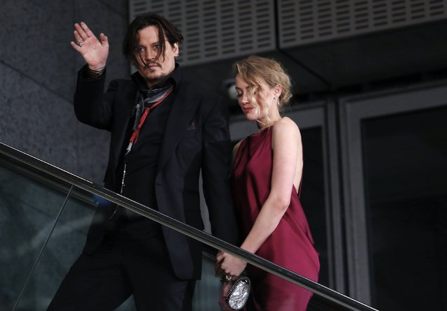 """Actor Johnny Depp waves to fans next to Amber Heard as they leave the Japan premiere of """"Mortdecai"""" in Tokyo January 27, 2015. (Photo by Yuya Shino/Reuters)"""
