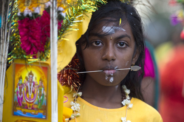 A Hindu devotee girl stands after getting her tongue pierced with a metal rod during the Thaipusam festival in Kuala Lumpur, Malaysia, Tuesday, February 3, 2015. Thaipusam, which is celebrated in honor of Hindu god Lord Murugan, is an annual procession by Hindu devotees seeking blessings, fulfilling vows and offering thanks. (Photo by Joshua Paul/AP Photo)