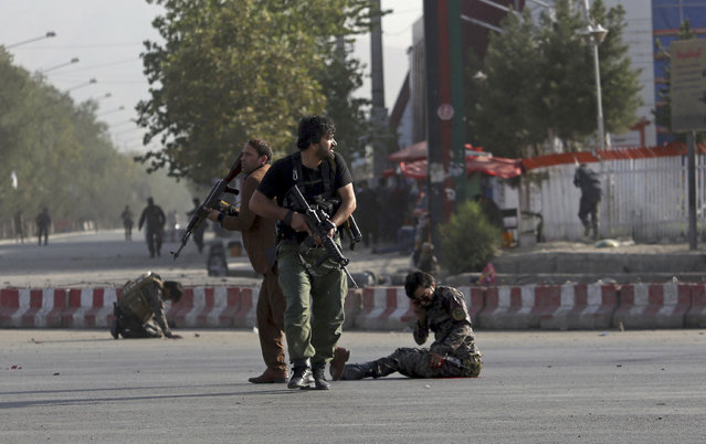 Afghan security personnel stand guard next to wounded comrades at the site of an attack near the Kabul International Airport, in Kabul, Afghanistan, Sunday, July 22, 2018. An Afghan spokesman said there has been a large explosion near the Kabul airport shortly after the country's controversial first vice president landed on his return from abroad. Gen. Abdul Rashid Dostum and members of his entourage were unharmed in the explosion on Sunday, which took place as his convoy had already left the airport. (Photo by Rahmat Gul/AP Photo)
