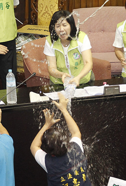 Ruling and opposition lawmakers fight with water on the legislature floor in Taipei, Taiwan, Friday, August 2, 2013. Taiwanese lawmakers exchanged punches and threw water at each other Friday ahead of an expected vote that would authorize a referendum on whether to finish a fourth nuclear power plant on this densely populated island of 23 million people. (Wally Santana/AP Photo)