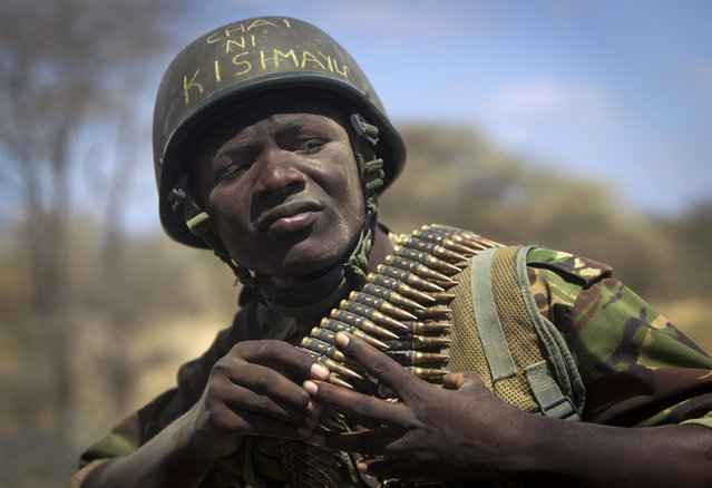 """Kenyan army soldier Nicholas Munyanya, wearing a helmet on which is written in Kiswahili """"Tea in Kismayo"""", referring to a key strategic Somali town under the control of al-Shabab, checks his ammunition belt near the town of Dhobley, currently under control by Kenyan military and Somali government forces, in Somalia Tuesday, February 21, 2012. (Photo by Ben Curtis/AP Photo)"""