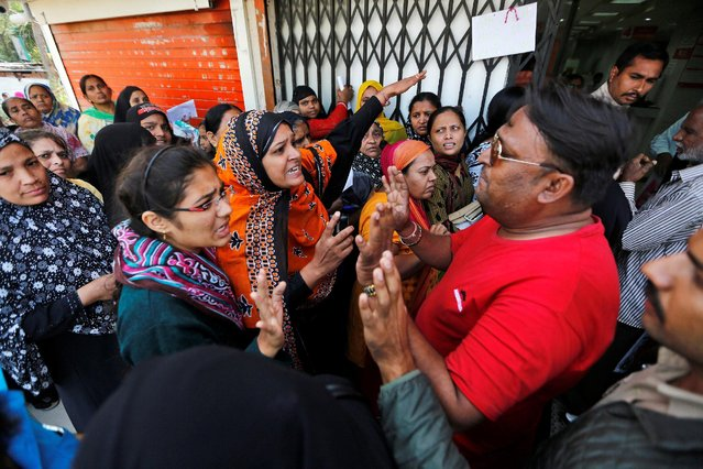 Women argue with bank employees after an ATM machine ran out of cash outside a bank in Ahmedabad, India, November 16, 2016. (Photo by Amit Dave/Reuters)