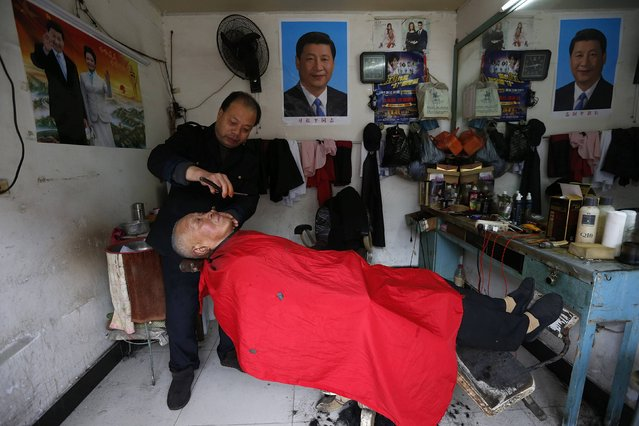 A barber shaves the face of his customer next to posters of Chinese President Xi Jinxing and his wife Peng Liyuan, at his barber shop in Yongjia county, Zhejiang province January 29, 2015. (Photo by William Hong/Reuters)