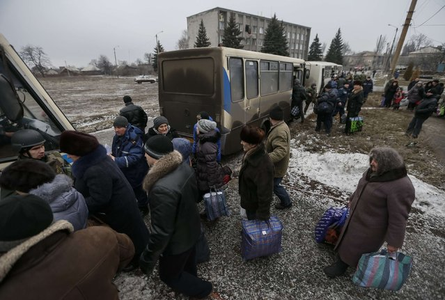 Members of the Ukrainian armed forces assist local residents onto a bus, to flee the military conflict, in Debaltseve, eastern Ukraine, February 6, 2015. (Photo by Gleb Garanich/Reuters)