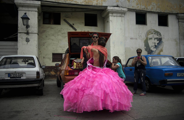 "In this December 3, 2015 photo, Gladys Barroso Quintana, who lives in Cuba, changes behind her parents' car from a traditional quinceanera dress to a more modern one, in a street decorated with a mural of Cuban revolutionary leader Ernesto ""Che"" Guevara in Havana, Cuba. Quinceanera packages at most studios in Cuba start around $150 and include professional hair and makeup artists, scenic Havana backdrops and multiple wardrobe changes – a bargain compared to similar services in the U.S. that typically start at about $1,000. (Photo by Ramon Espinosa/AP Photo)"