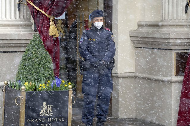Snow falls as a police officer stands in front of the Grand Hotel Wien where closed-door nuclear talks with Iran take place in Vienna, Austria, Tuesday, April 6, 2021. Foreign ministry officials from the countries still in the accord, the so-called Joint Comprehensive Plan of Action, are meeting in Vienna to push forward efforts to bring the United States back into the 2015 deal on Iran's nuclear program. (Photo by Florian Schroetter/AP Photo)