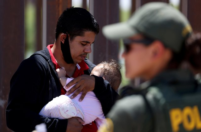 A man from Brazil holds his nine-month-old daughter as they wait to be transported by the U.S. Border Patrol after crossing into the United States from Mexico in Andrade, California, U.S., April 19, 2021. (Photo by Jim Urquhart/Reuters)