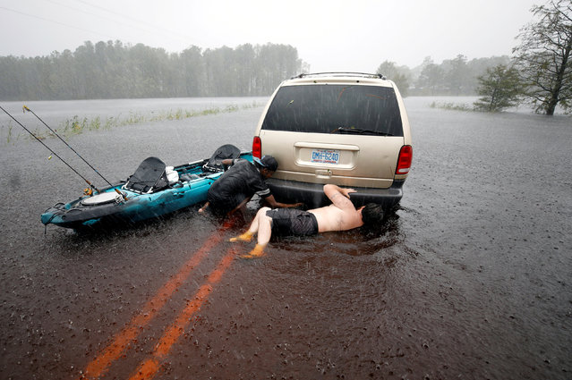 A shirtless Jordan McKeon and his friend Nathaniel Harrison try to free a stalled car that became stranded in rising flood waters while trying to cross an inundated bridge, after Hurricane Florence struck in Boiling Spring Lakes, North Carolina, U.S., September 15, 2018. (Photo by Jonathan Drake/Reuters)