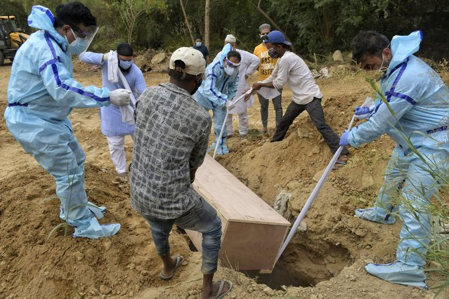 """The incumbent conservative Madrid president Isabel Diaz Ayuso casts her vote during the regional election in Madrid, Spain, Tuesday, May 4, 2021. (Photo by Bernat Armangue/AP Photo)    [img alt=""""Relatives bury the body of a COVID-19 victim at a graveyard in New Delhi, India, Tuesday, May 4, 2021. India's official count of coronavirus cases surpassed 20 million Tuesday, nearly doubling in the past three months, while deaths officially have passed 220,000. Staggering as those numbers are, the true figures are believed to be far higher, the undercount an apparent reflection of the troubles in the health care system. (Photo by Ishant Chauhan/AP Photo)"""