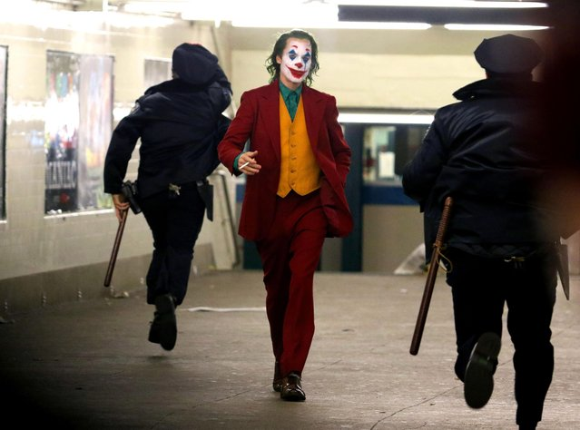 """JOKER"" movie production tries to hide Joaquin Phoenix's clown make-up and green hair with umbrella and a long black cloth over his head as he was walking with the help of assistant and bodyguard to the set of ""JOKER"" filming at a Bronx train station on September 22, 2018. (Photo by The Mega Agency)"