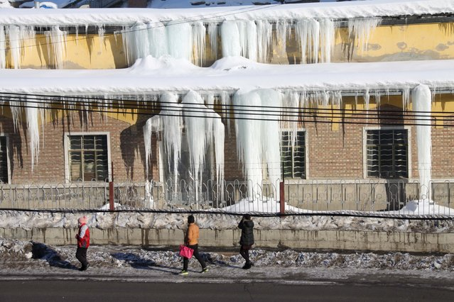 People look at icicles hanging on the roof of a factory building in Altay, Xinjiang Uighur Autonomous Region, China, January 12, 2016. (Photo by Reuters/Stringer)