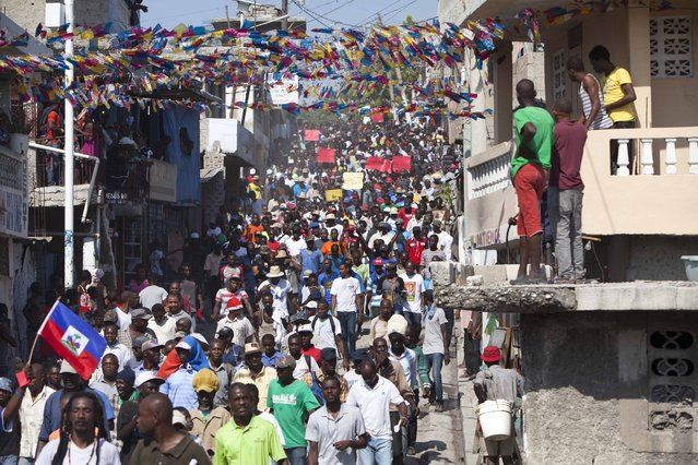 In this Monday, January 18, 2016 photo, protesters chant anti-government slogans during a protest demanding the cancellation of the upcoming elections, in Port-au-Prince, Haiti. Just two days before the presidential and legislative runoffs, the spokesman for Haiti's electoral council said Friday, January 22, 2016, that the council has agreed to postpone for a second time. (Photo by Dieu Nalio Chery/AP Photo)