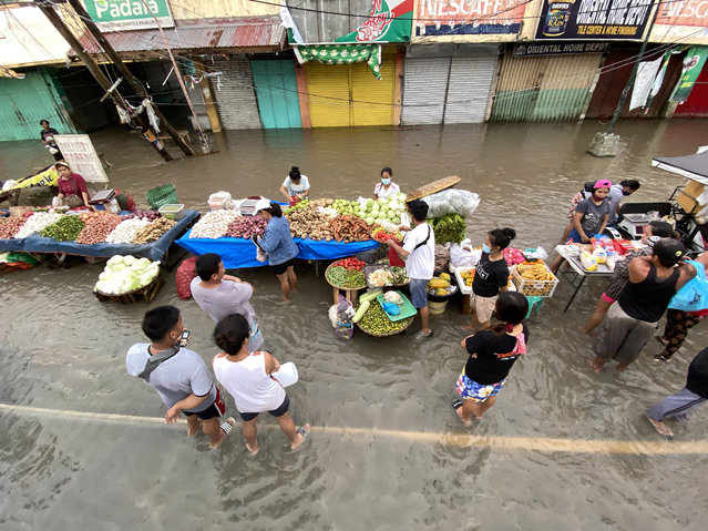 Filipinos sell food along a flooded road in the typhoon-hit town of Nabua, Camarines Sur, Philippines, 01 November 2020. Super Typhoon Goni, with winds forecasted to reach over 240 kilometers per hour, made landfall on 01 November 2020, in the Philippine provinces of Albay, Camarines Sur and Quezon. (Photo by Francis R. Malasig/EPA/EFE)