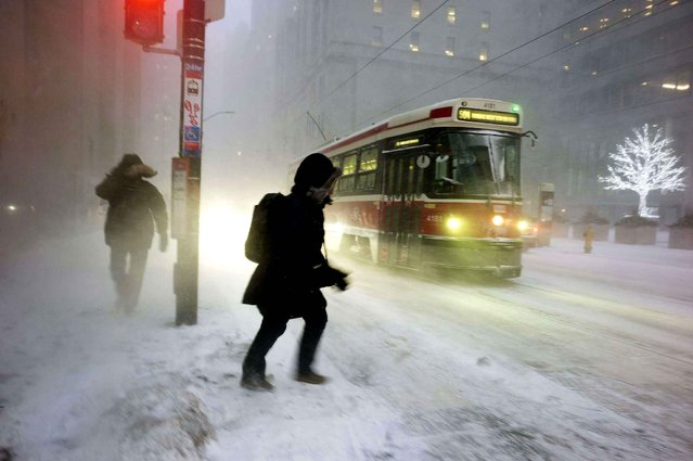 A person makes their way to a streetcar as snow flies through the air during a squall in downtown Toronto, on Thursday, December 15, 2016. (Photo by Graeme Roy/The Canadian Press via AP Photo)