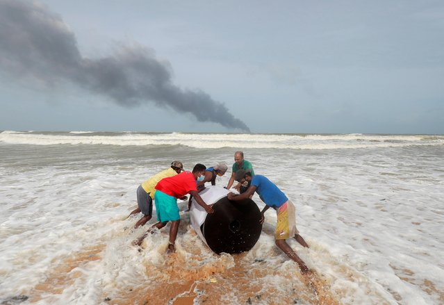 Smoke rises from a fire onboard the MV X-Press Pearl container ship in the seas off the Colombo Harbour as villagers push the cargo spilled from it on a beach in Ja-Ela, Sri Lanka on May 26, 2021. (Photo by Dinuka Liyanawatte/Reuters)