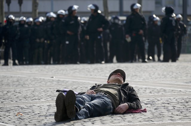 A protester lies on the pavement in front of a group of German riot police officers near the European Central Bank (ECB) building before the official opening of its new headquarters in Frankfurt March 18, 2015. (Photo by Kai Pfaffenbach/Reuters)