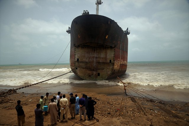 People stand next to a ship, containing tonnes of hazardous mercury-mixed oil, as it was allowed to anchor at Gadani ship-breaking yard in Gadani, Pakistan, 28 May 2021. Authorities have launched an investigation into the anchoring of a ship at the Gadani shipbreaking yard despite Interpol's warning that the ship contains dangerous chemicals. (Photo by Rehan Khan/EPA/EFE)