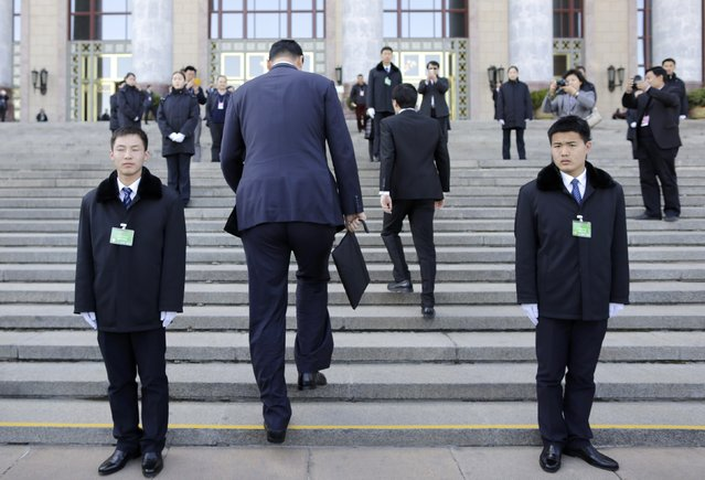 Former NBA basketball player Yao Ming (2nd L) walks past security personnel as he arrives for the closing session of the Chinese People's Political Consultative Conference (CPPCC) outside the Great Hall of the People, in Beijing, March 13, 2015. (Photo by Jason Lee/Reuters)