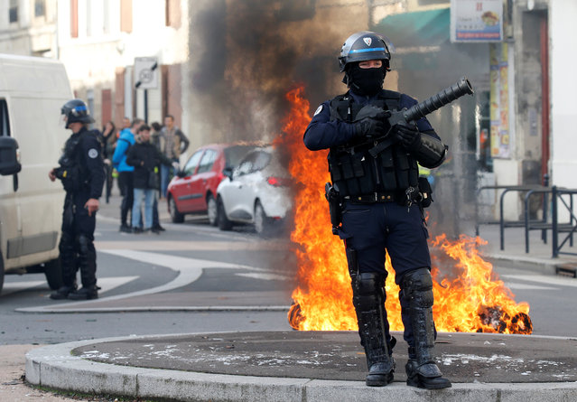 A French riot policeman stands next to a burning trash container as youth and students protest against reform plan in the streets of Bordeaux, France on December 5, 2018. (Photo by Regis Duvignau/Reuters)