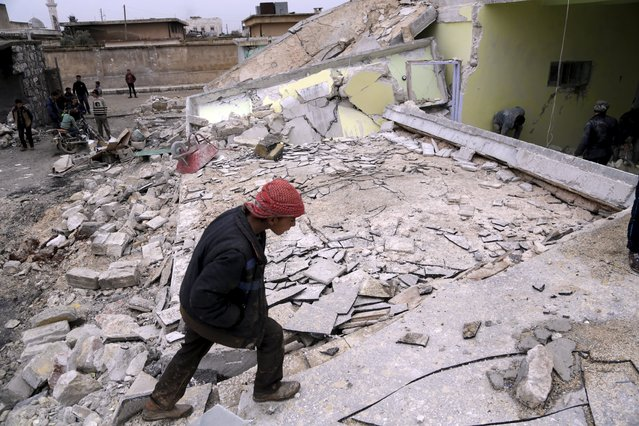 A boy inspects his school, damaged in what activists said was an air strike carried out yesterday by the Russian air force in Injara town, Aleppo countryside, Syria January 12, 2016. (Photo by Khalil Ashawi/Reuters)